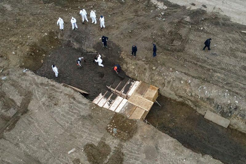ειδικά εξοπλισμένοι εργάτες τοποθετούν τα φέρετρα στον ομαδικό τάφο